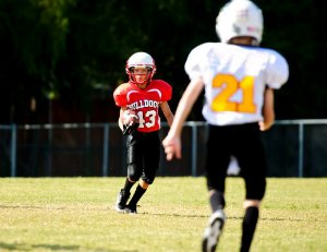 Youth football boy running the ball.